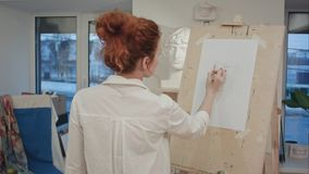 Female art student drawing plaster cast on easel. Professional shot on BMCC RAW with high dynamic range. You can use it e.g. in your commercial video, business stock photos