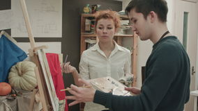 Female art teacher analyzing painting with her male student stock footage