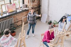 Female Art Teacher in Class. Full length portrait of elegant smiling female teacher watching group of students painting at easels in art class, copy space royalty free stock image