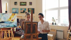 Female art teacher is working with good-looking young girl student painting picture giving advice standing in front of stock video footage