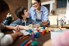 Female Art Teacher Working with Kids. Portrait of smiling art teacher working with kids painting pictures in art class, copy space stock photo