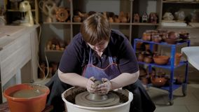Female artisan is doing process of throwing of clay blank on rotating turntable in pottery shop with ceramic. Pots in background stock video