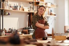 Female Artisan Posing. Warm toned portrait of smiling female artisan standing with arms crossed while posing in workshop royalty free stock photo