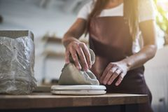 Female artisan weighing blocks of clay in her ceramic workshop royalty free stock images