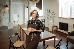 Female artist in apron holds a mug