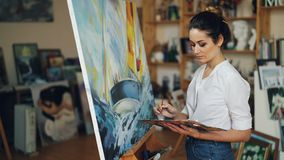 Female artist is concentrated on work painting beautiful picture sea and boat with oil paints working alone in studio stock footage