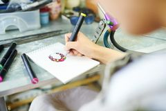 Female Artist Drawing Sketch. Close up of unrecognizable female artist drawing sketch ready to create beautiful jewelry in glassworking studio stock images