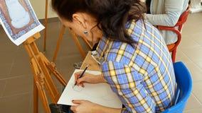 Female artist draws a pencil sketch in art studio Royalty Free Stock Image