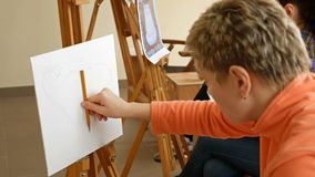 Female artist draws a pencil sketch in art studio. Female artist draws a pencil sketch drawing on canvas easel in art studio. Student girl learning to draw and stock footage
