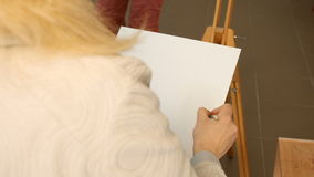 Female artist draws a pencil sketch in art studio. Female artist draws a pencil sketch drawing on canvas easel in art studio. Student girl learning to draw and stock video