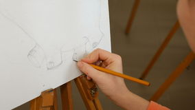 Female artist draws a pencil sketch in art studio. Female artist draws a pencil sketch drawing on canvas easel in art studio. Student girl learning to draw and stock video footage