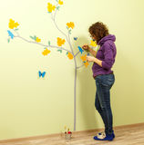 Female artist draws tree, butterflies and birds on the wall Stock Image
