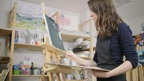 Imagination on canvas. Female artist expressing herself with creating new paintings. She has so many ideas to come alive in this studio stock video footage