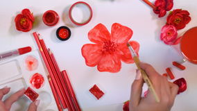 Female artist hands drawing red flower. Creative artist desk from above.