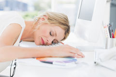 Female artist with head resting on keyboard Royalty Free Stock Photos