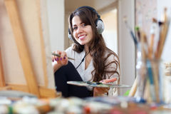 Female artist  in headphones paints picture on canvas Royalty Free Stock Photos