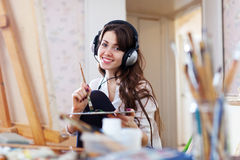 Female artist in headphones paints picture Royalty Free Stock Image