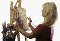 Female artist in her fifties painting Stock Image