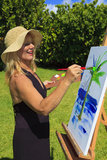 Female artist in her fifties painting Royalty Free Stock Image