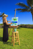 Female artist in her fifties painting. A female artist in her fifties creating a painting outside on canvas of a palm tree and the ocean in Lanikai, Hawaii Royalty Free Stock Images