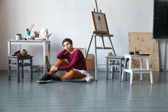 Female artist in her spacious white studio working with watercolor painting Stock Photography