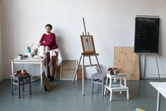 Female artist in her spacious white studio Stock Photography