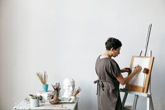 Female artist in her spacious white studio. Working with watercolor painting.  Natural lighting. Disclosure of creativity concept. Horizontal composition with Royalty Free Stock Image