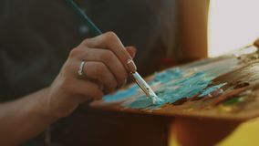 Female artist holding dirty palette with paints. Woman hand holding brush stock footage
