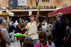 A female artist juggler and medieval musicians and people around them at the medieval fair in Elche, Spain. stock photos
