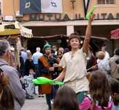 A female artist juggler is representing a performance in a medieval fair stock photography