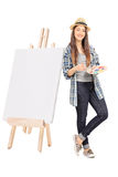 Female artist leaning on a blank canvas Stock Image