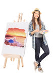 Female artist leaning on an easel with painting. Isolated on white background stock photography