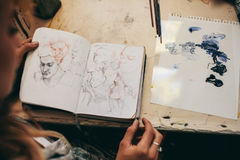 Female artist looking at sketches in her studio. Top view of female artist looking at sketches in her studio. Close up of woman painter working in her workshop stock images