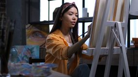 Female artist making a painting at art studio. Creative attractive mixed race female artitist making a painting on canvas with acrylic paints in own art studio stock footage