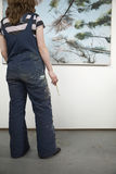 Female Artist With Paintbrush Looking At Painting Royalty Free Stock Photography