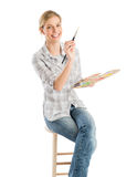 Female Artist With Paintbrush And Palette Sitting On Stool Royalty Free Stock Photo