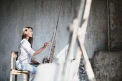 Female artist with paintbrushes and palette in her hands painting in studio. Stock Photo