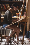 Female artist painter. In her studio.Charcoal drawings stock images