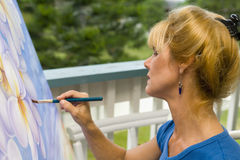 A female artist painting on canvas Royalty Free Stock Photos