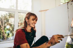 Female artist painting on canvas and smiling. Indoor shot of female artist painting on canvas in studio and smiling. Happy young woman painter painting in her stock images