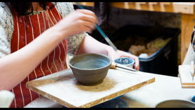 Female artist painting on earthenware bowl stock video footage