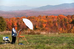 Female artist painting fall foliage, New Hampshire royalty free stock photo