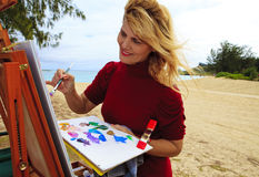 Female artist painting outdoors. At a beach in hawaii Stock Photo