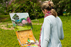 Female artist painting outdoors. Back view of a female artist working on a trestle and easel painting with oils and acrylics  outdoors painting a garden scene Royalty Free Stock Photos