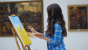 Female artist painting a picture on canvas. Art gallery background. 4K. Female artist painting a picture on canvas. Art gallery background stock video footage