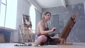 Female artist painting picture in studio sitting on the floor stock video