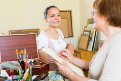 Female artist painting portrait of woman Royalty Free Stock Image