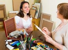 Female artist painting portrait of woman Stock Image