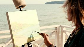 Female artist painting a seascape outdoors stock footage