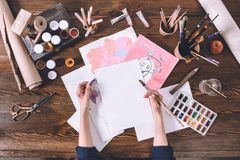 Female artist painting sketches at workplace with paints and brushes stock photos